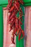 Σειρές των πιπεριών τσίλι που κρεμούν έξω από το παράθυρο στο χωριό στην Κροατία Στοκ Εικόνες