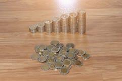 Σειρές των σωρών νομισμάτων στο ξύλινο πάτωμα σύμβολο ποσοστού χρημάτων χεριών τραπεζικής έννοιας Στοκ Φωτογραφίες