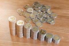 Σειρές των σωρών νομισμάτων στο ξύλινο πάτωμα σύμβολο ποσοστού χρημάτων χεριών τραπεζικής έννοιας Στοκ Εικόνες