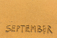 Σεπτέμβριος - επιγραφή λέξης στη χρυσή παραλία άμμου Στοκ Εικόνα