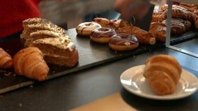 Σερβιτόρα που ένας croissant στον πελάτη απόθεμα βίντεο