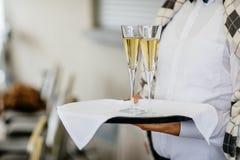 Σερβιτόρα που κρατά ένα πιάτο των γυαλιών σαμπάνιας και κρασιού σε κάποιο Φε στοκ φωτογραφίες