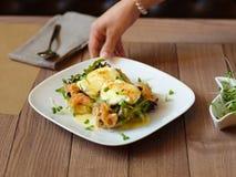 Σερβιτόρα που μια κινηματογράφηση σε πρώτο πλάνο μεσημεριανού γεύματος Λαθραία αυγά σε έναν πίνακα backg Στοκ Φωτογραφία