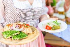 Σερβιτόρα που τα βαυαρικά τρόφιμα στον κήπο μπύρας Στοκ εικόνες με δικαίωμα ελεύθερης χρήσης