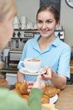 Σερβιτόρα στον εξυπηρετώντας πελάτη καφέδων με τον καφέ Στοκ εικόνες με δικαίωμα ελεύθερης χρήσης
