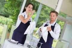Σερβιτόροι που θέτουν τους πίνακες στο εστιατόριο γαστρονομίας Στοκ Φωτογραφία
