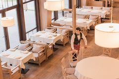 Σερβιτόρος που βάζει τις καρέκλες γύρω από τον πίνακα Στοκ φωτογραφία με δικαίωμα ελεύθερης χρήσης