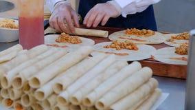 Σερβιτόρος που μαγειρεύει το μεξικάνικο burrito Ο σερβιτόρος δίνει το burrito τυλίγματος συμπληρώνοντας tortilla απόθεμα βίντεο