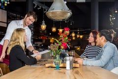 Σερβιτόρος που παρουσιάζει τις επιλογές στους πελάτες στο φραγμό Στοκ Εικόνες