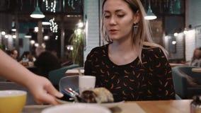 Σερβιτόρος που φέρνει μια νόστιμη μπριζόλα ψαριών για την ελκυστική νέα γυναίκα στο εστιατόριο κίνηση αργή φιλμ μικρού μήκους