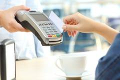 Σερβιτόρος που χρεώνει με τον αναγνώστη πιστωτικών καρτών σε έναν φραγμό Στοκ Εικόνα