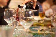 Σερβιτόρος που χύνει το κόκκινο κρασί στα γυαλιά Στοκ Φωτογραφία