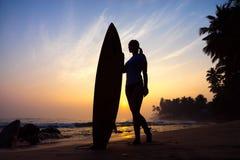 Σερφ κοριτσιών Surfer που εξετάζει το ωκεάνιο ηλιοβασίλεμα παραλιών Σκιαγραφία W Στοκ φωτογραφίες με δικαίωμα ελεύθερης χρήσης