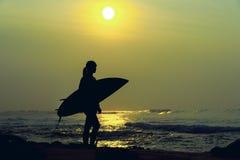Σερφ κοριτσιών Surfer που εξετάζει το ωκεάνιο ηλιοβασίλεμα παραλιών Σκιαγραφία W Στοκ Εικόνες