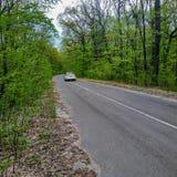 Σε έναν δασικό δρόμο το αυτοκίνητο οδηγεί μακριά στοκ εικόνα με δικαίωμα ελεύθερης χρήσης