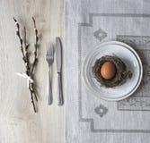 Σε έναν πίνακα μια πετσέτα με ένα πιάτο ένα μαχαίρι δικράνων μια φωλιά με ένα αυγό ενός κλαδίσκου ιτιών Στοκ Φωτογραφίες