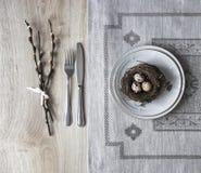 Σε έναν πίνακα μια πετσέτα με ένα πιάτο ένα μαχαίρι δικράνων μια φωλιά με ένα αυγό ενός κλαδίσκου ιτιών Στοκ φωτογραφίες με δικαίωμα ελεύθερης χρήσης