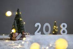 Σε έναν χιονισμένο τομέα κάτω από fir-trees, το σκυλί κοιμάται στα δώρα και στην απόσταση είναι τα σχήματα το 2018 Στοκ φωτογραφία με δικαίωμα ελεύθερης χρήσης