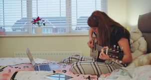 Σε έναν όμορφο έφηβο δωματίων η έναρξη κοριτσιών να παίζουν σε μια κιθάρα που βάζει στο κρεβάτι πολύ την συγκέντρωσε που ξοδεύει  απόθεμα βίντεο
