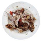 Σε ένα άσπρο κεραμικό πιάτο ένας σωρός των δερμάτων και των αποβλήτων κόκκαλων από το α Στοκ Εικόνα