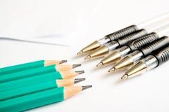 Σε ένα άσπρο υπόβαθρο είναι απλοί από γραφίτη μολύβια και στυλοί μπροστά από τα μολύβια, φύλλα εγγράφου στο υπόβαθρο στοκ φωτογραφίες
