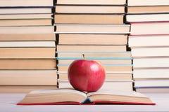 Σε ένα ανοικτό βιβλίο στο hardcover υπάρχει ένα κόκκινο μήλων Στοκ Φωτογραφία