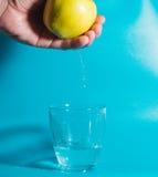 Σε ένα γυαλί των μειωμένων πτώσεων νερού του νερού με τη Apple διαθέσιμη Στοκ φωτογραφία με δικαίωμα ελεύθερης χρήσης