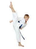 Σε ένα λευκό αγόρι υποβάθρου ο αθλητής σε ένα κιμονό εκτελεί μια εγκύκλιο ποδιών λακτίσματος που μονώνεται Στοκ εικόνα με δικαίωμα ελεύθερης χρήσης