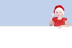 Σε ένα κόκκινα φόρεμα και ένα καπέλο Άγιου Βασίλη ένα μικρό κορίτσι παρουσιάζει ένα δάχτυλο σε έναν πίνακα διαφημίσεων Στοκ Φωτογραφία