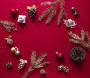 Σε ένα κόκκινο υπόβαθρο σμέουρων, τα Χριστούγεννα και τις νέες διακοσμήσεις έτους και τους επιχρυσωμένους κλάδους του χριστουγενν Στοκ Εικόνες