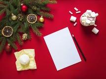 Σε ένα κόκκινο υπόβαθρο των πράσινων κλάδων έλατου, που διακοσμείται δίπλα σε ένα άσπρο φύλλο και ένα μαύρο μολύβι, μια κούπα με  Στοκ Φωτογραφία