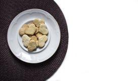 Σε ένα λευκό το υπόβαθρο σε μια σκοτεινή πετσέτα είναι ένα πιάτο με τα μπισκότα υπό μορφή καρδιάς Στοκ Εικόνα