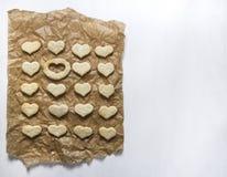 Σε ένα λευκό το υπόβαθρο σε χαρτί ψησίματος βρίσκεται ένα μπισκότο με μορφή μιας καρδιάς και μια θέση είναι κενή Στοκ εικόνα με δικαίωμα ελεύθερης χρήσης