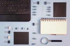 Σε ένα μπλε υπόβαθρο, τακτοποιημένα σχεδιασμένο σημειωματάριο, προμήθειες σημειωματάριων και γραφείων Ασυνήθιστο επιχειρησιακό υπ Στοκ Εικόνες