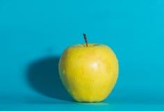 Σε ένα μπλε υπόβαθρο η κίτρινη Apple, κλείστε επάνω Στοκ Εικόνες