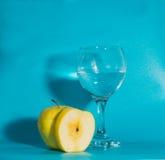 Σε ένα μπλε υπόβαθρο η κίτρινη Apple με ένα ποτήρι του νερού Στοκ φωτογραφία με δικαίωμα ελεύθερης χρήσης