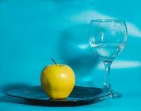 Σε ένα μπλε υπόβαθρο η κίτρινη Apple στο πιάτο με ένα γυαλί του W Στοκ Εικόνες