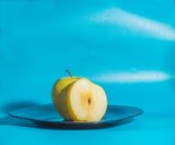 Σε ένα μπλε υπόβαθρο η κίτρινη Apple στο πιάτο Στοκ εικόνες με δικαίωμα ελεύθερης χρήσης