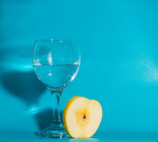 Σε ένα μπλε υπόβαθρο και μια φέτα της κίτρινης Apple με ένα γυαλί Στοκ Εικόνες