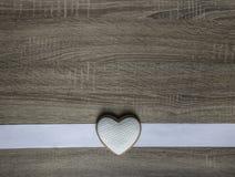 Σε ένα ξύλινο υπόβαθρο ένα άσπρο λωρίδα και μπισκότα υπό μορφή καρδιάς Στοκ εικόνες με δικαίωμα ελεύθερης χρήσης