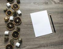 Σε ένα ξύλινο υπόβαθρο ένα άσπρο φύλλο και ένα μαύρο μολύβι και στο αριστερό ένα σχεδιάγραμμα των ξηρών πορτοκαλιών, σφαίρες, mar Στοκ Εικόνες