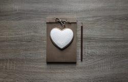 Σε ένα ξύλινο υπόβαθρο βρίσκεται ένα επιστολόχαρτο τεχνών που σε το το μολύβι καρδιών μπισκότων καφετί Στοκ εικόνα με δικαίωμα ελεύθερης χρήσης