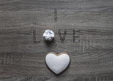 Σε ένα ξύλινο υπόβαθρο βρίσκεται η αγάπη λέξης συνδετήρων εγγράφου αντί της άμορφης τσαλακωμένης καρδιάς μπισκότων εγγράφου γραμμ Στοκ φωτογραφίες με δικαίωμα ελεύθερης χρήσης
