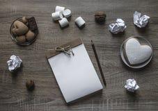 Σε ένα ξύλινο υπόβαθρο βρίσκεται μια marshmallow μολυβιών καρδιών μπισκότων πιάτων σημειωματάριων τεχνών scrapbooking καφετιά μέν Στοκ φωτογραφίες με δικαίωμα ελεύθερης χρήσης