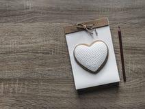 Σε ένα ξύλινο υπόβαθρο βρίσκεται ένα σημειωματάριο τεχνών με ένα τόξο σχοινιών που σε το το μολύβι καρδιών μπισκότων καφετί Στοκ Εικόνα