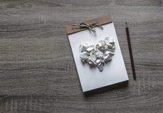 Σε ένα ξύλινο υπόβαθρο βρίσκεται ένα scrapbooking μολύβι σημειωματάριων τεχνών σε μια καρδιά σημειωματάριων του τσαλακωμένου εγγρ Στοκ Φωτογραφίες