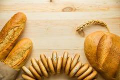 Σε ένα ξύλινο υπόβαθρο δύο τηγανισμένα αρωματικά baguettes, bagels στοκ εικόνες