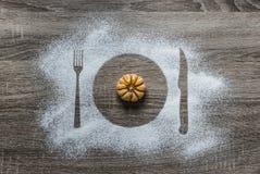 Σε ένα ξύλινο υπόβαθρο με την κονιοποιημένη σκόνη χιονισμένη με τη σκιαγραφία οι συσκευές πιάτων δικράνων μαχαιριών βρίσκονται μα Στοκ Εικόνες