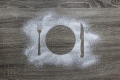 Σε ένα ξύλινο υπόβαθρο με την κονιοποιημένη σκόνη χιονισμένη με τις συσκευές μαχαιριών δικράνων πιάτων σκιαγραφιών Στοκ Εικόνα