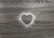 Σε ένα ξύλινο υπόβαθρο με το κονιοποιημένο χιόνι σκονών μια σκιαγραφία της καρδιάς Στοκ Εικόνες